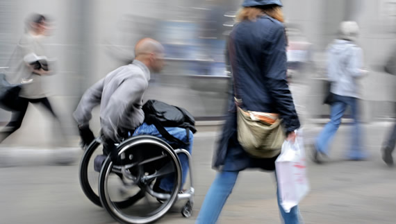 a men with wheelchair moving among other people